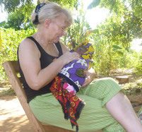 Frau Güpner unter einem Moringa Baum in Namibia mit Baby im Arm