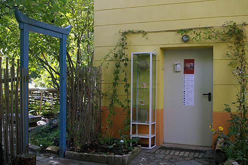 Atelier Eingang blaues Tor mit Vitrine und Keramikarbeit