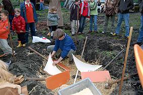 Keramik in Sägemehlbett für den Grubenbrand legen