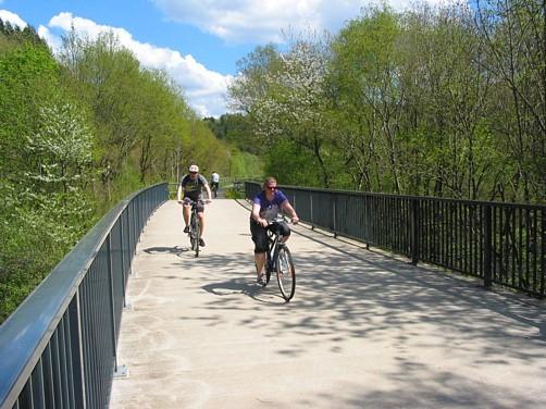 Pluwig. Früher Bahntrasse, heute Teil des Ruwer-Hochwald-Radwegs. Radfahrer überqueren die Krebsensbrücke.