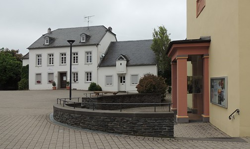 Pluwig. Kirchplatz. Rondell vor dem Portal von St. Johannes d.T.. Im Hintergrund das alte Pfarrhaus.