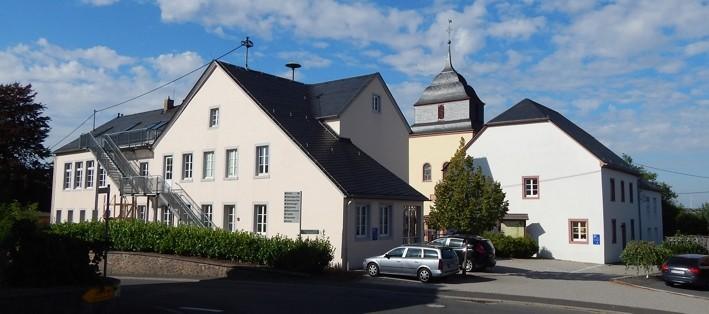 Der Kirchplatz von außen, vom Geizenburger Kapellchen aus: Links die Kindertagesstätte, in der Mitte St. Johannes der Täufer, rechts das Johannesberg-Haus. Innerhalb dieses architektonischen Ensembles liegt der Kirchplatz.