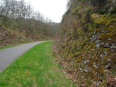 Die alte Bahntrasse wurde streckenweise durch den Schiefer gesprengt. Vorne rechts: Untermauerung zur Felssicherung.
