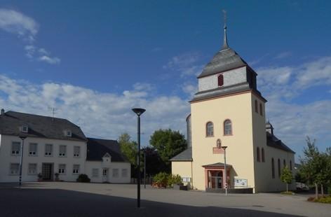 Pluwig. Kirchplatz. Links das Pfarrhaus, rechts St. Johannes der Täufer.