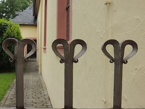 Pluwig, St. Johannes d.T.. (Moderne) Schmiedearbeit am Tor zum Pfarrgarten.