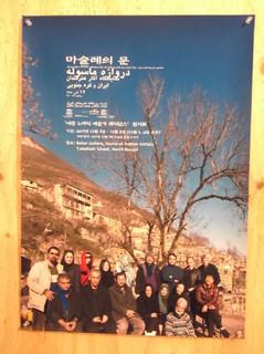 事務所の壁にイランでのシンポのポスター(ソウルでリポート展開催)