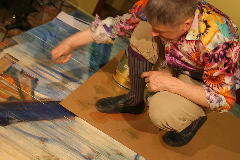 Igor Kormyshev is painting the big table inside the gallery's Cafeteria