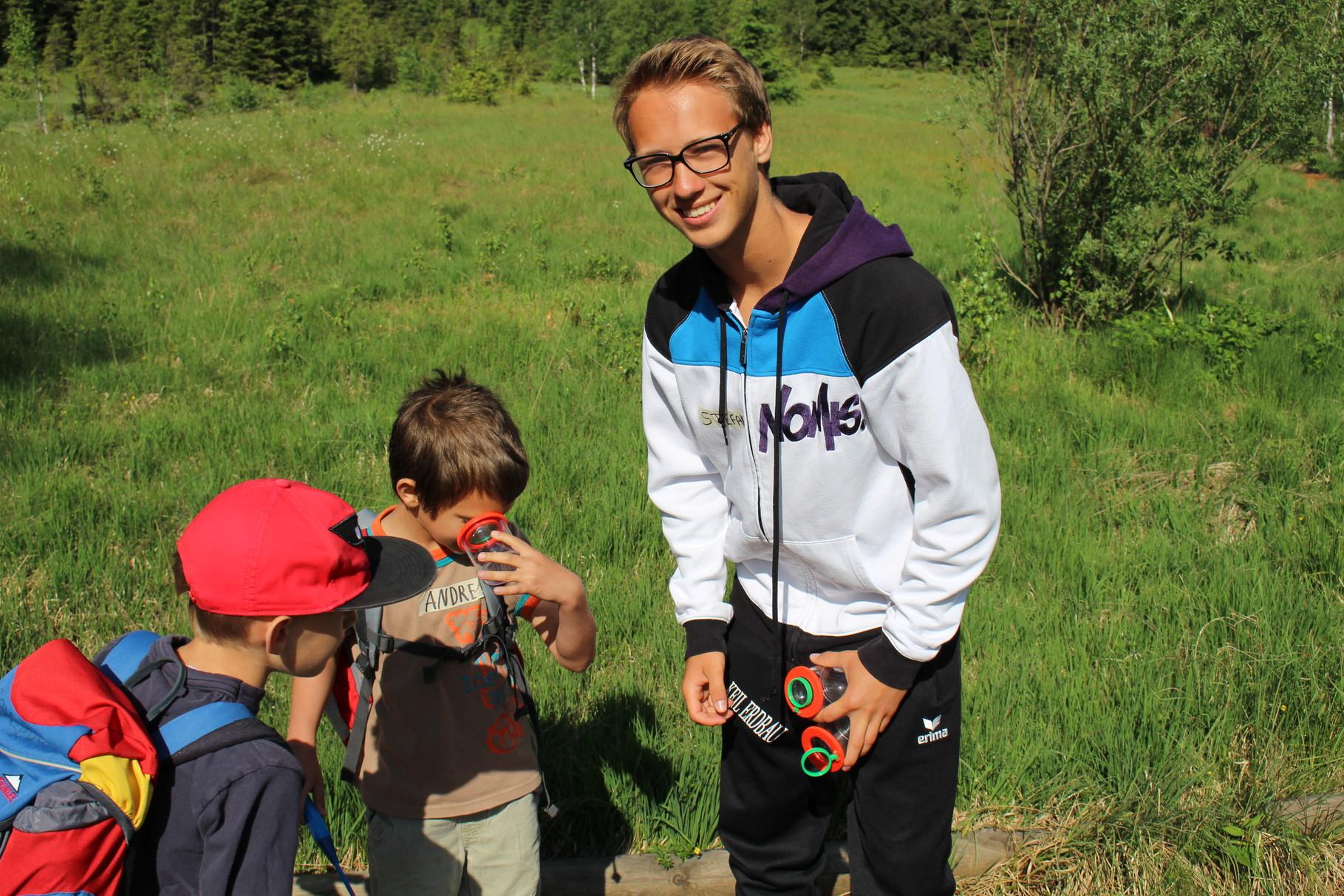 Unter der Becherlupe betrachten die Kinder der Volkschule Mittersill selbst gefangenen Insekten aus dem Moor - Hilfestellung leisten ihnen dabei die SchülerInnen vom BORG Mittersill (im Bild rechts Stefan Breuer, Klasse 6c)