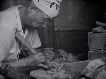 昭和初期頃の三代目の作業風景。ノミを肩に当てて彫る伝統姿勢。ノミの写真はページ背景にある(用途によって使い分ける)。