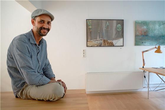 Imed Ben Tahar neben zweien seiner Bilder. Die Motive findet er erst im Akt des Malens. Bild: Metz