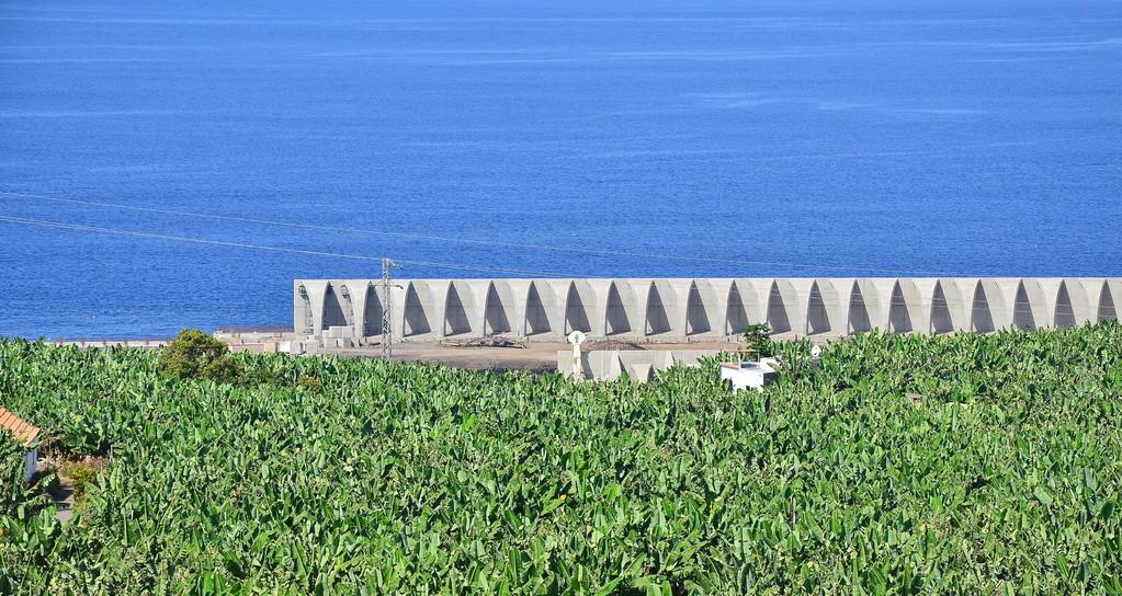Wuchtiger und länger als die im Rücken stehenden Elemente der alten Schutzwand, ist die neue Wellenbrecherwand zum Schutz des vergrößerten Hafens und Schiffsanlegers.