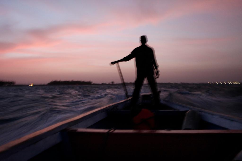 auf einer Piroge fahren die Männer über das Meer von den Senegal