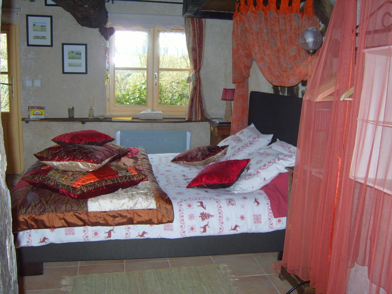 le lit est installé dans l'ancienne cheminée conservée avec sa hotte en torchis