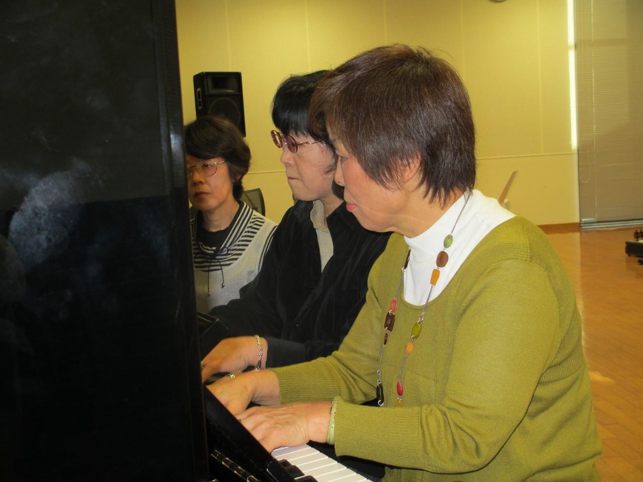 真剣表情のピアノの連弾