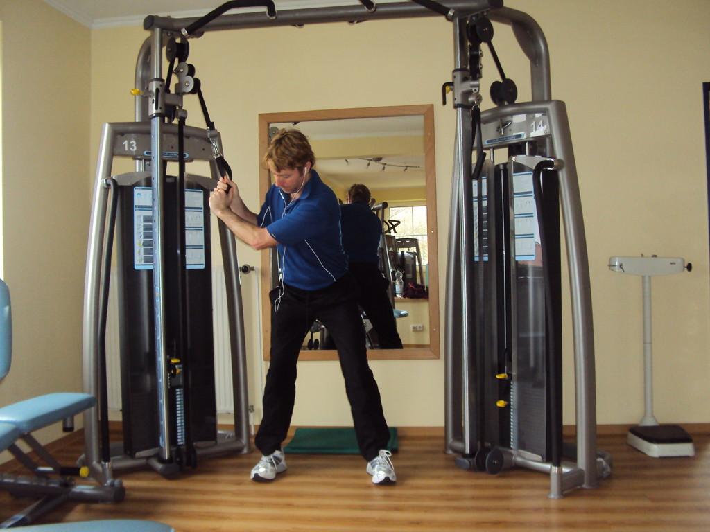 Bleiben Sie in Ihre Golf-Haltung mit dem Rücken an das Kabel-cross-Maschine.