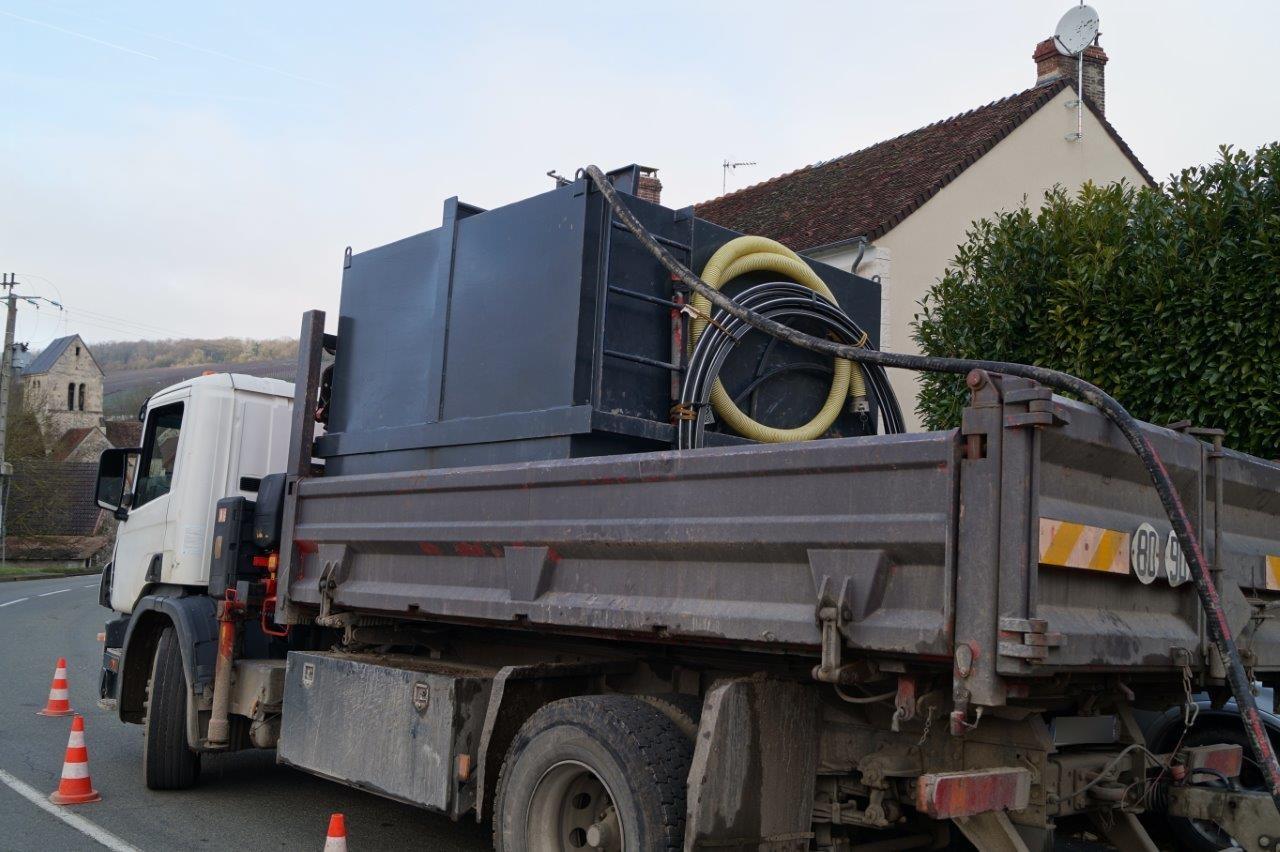 Un camion transporte un réservoir d'eau.