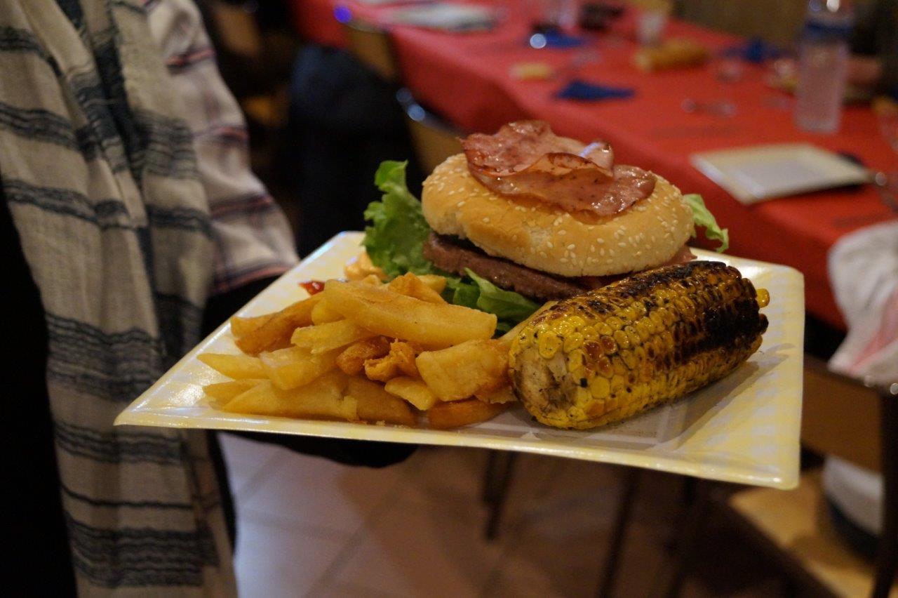 """Les buns (petits pains ronds) accompagnés du fameux """"side"""" : steack haché, bacon, salade, tomates, fromage, maïs, frites."""