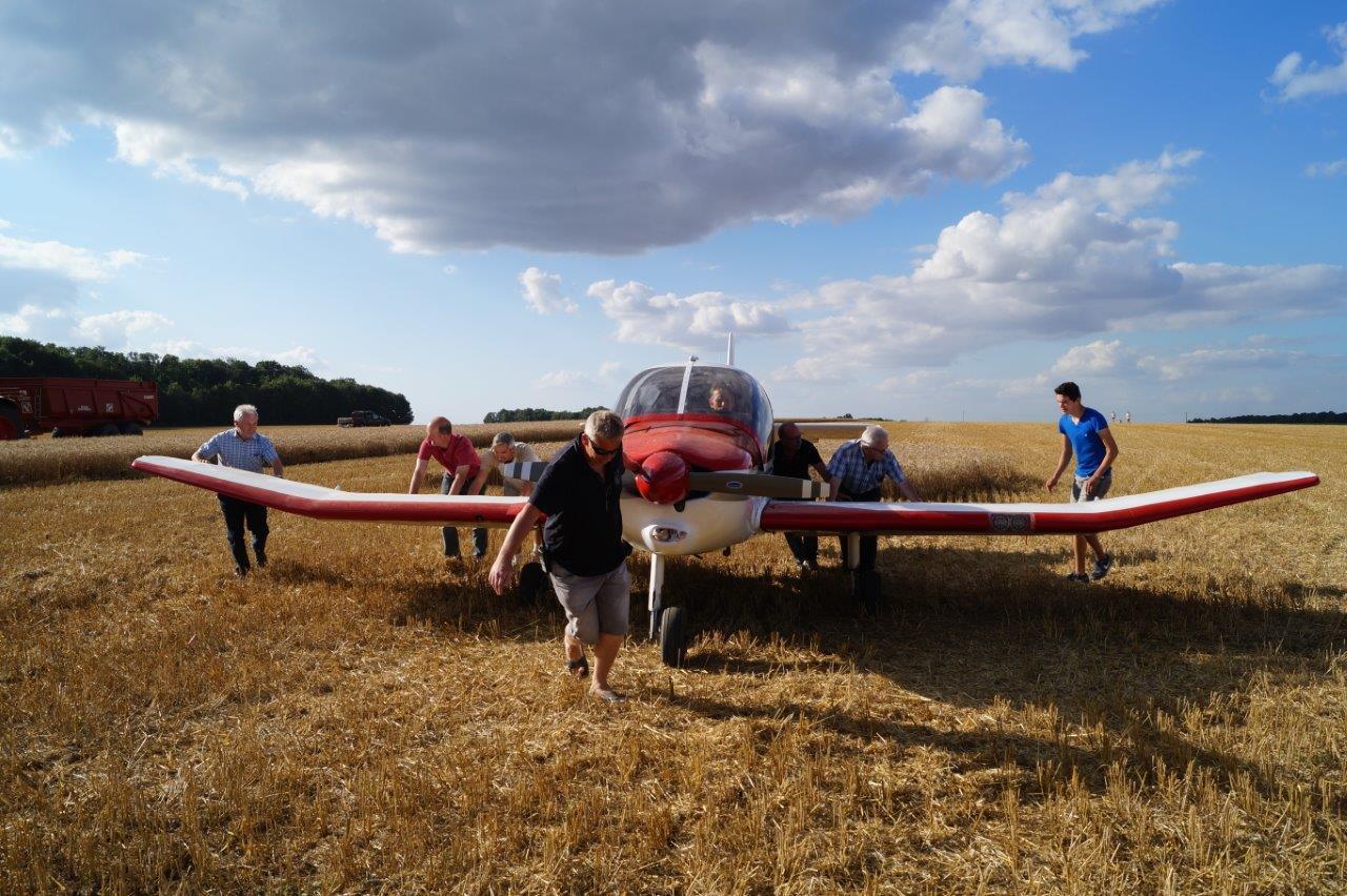 Adhérents de l'aéroclub, élus locaux et curieux emmènent l'appareil en bout de piste.