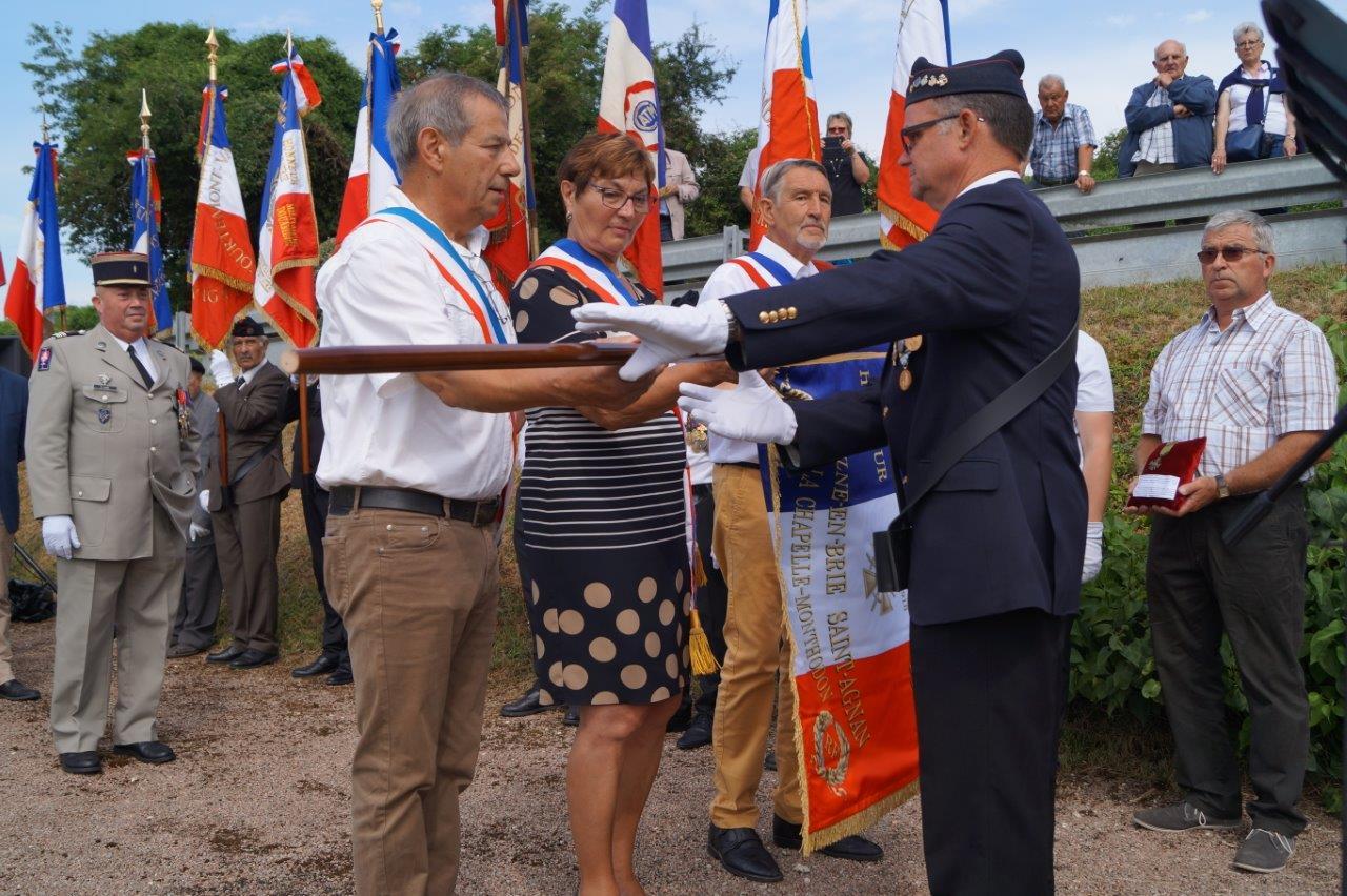 De gauche à droite : Bruno Lahouati, Jacqueline Picart et Pierre Troublé, adjoint au maire délégué de Saint-Agnan, remettent le drapeau de la commune Vallées-en-Champagne à Marcel Dartinet, porte-drapeau et ancien combattant...