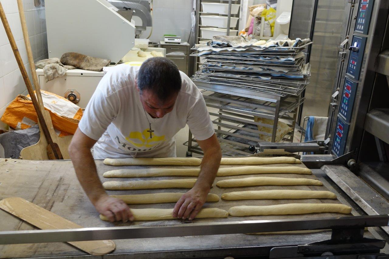 Dès la phase de fermentation terminée, le boulanger peaufine les baguettes avant d'enfourner.