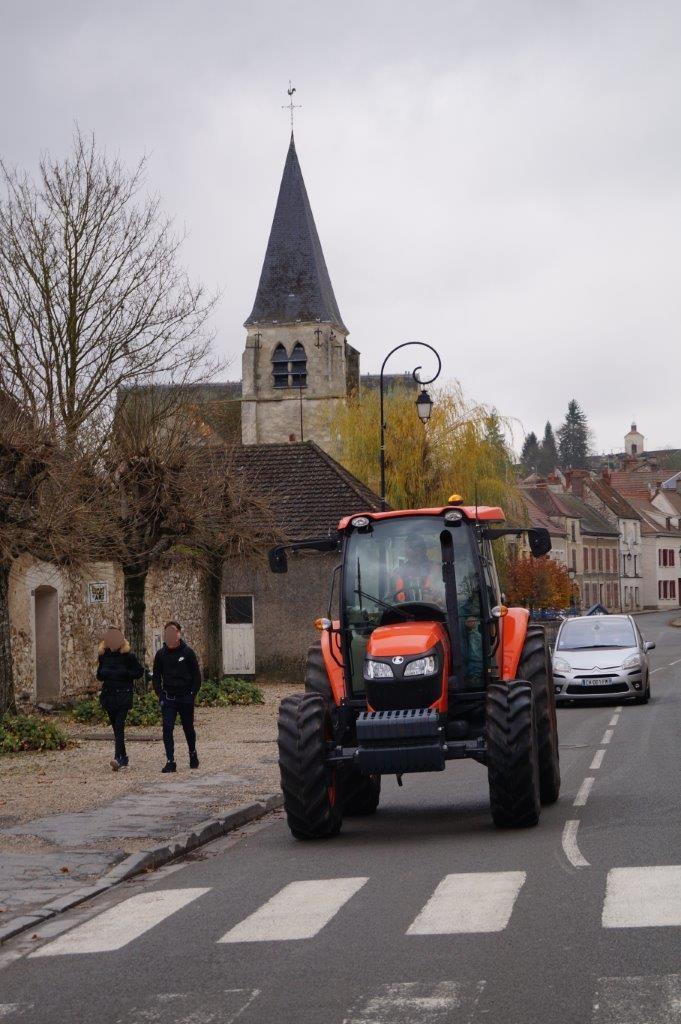 Le nouveau tracteur des employés municipaux se dirige vers la mairie pour l'arrosage.