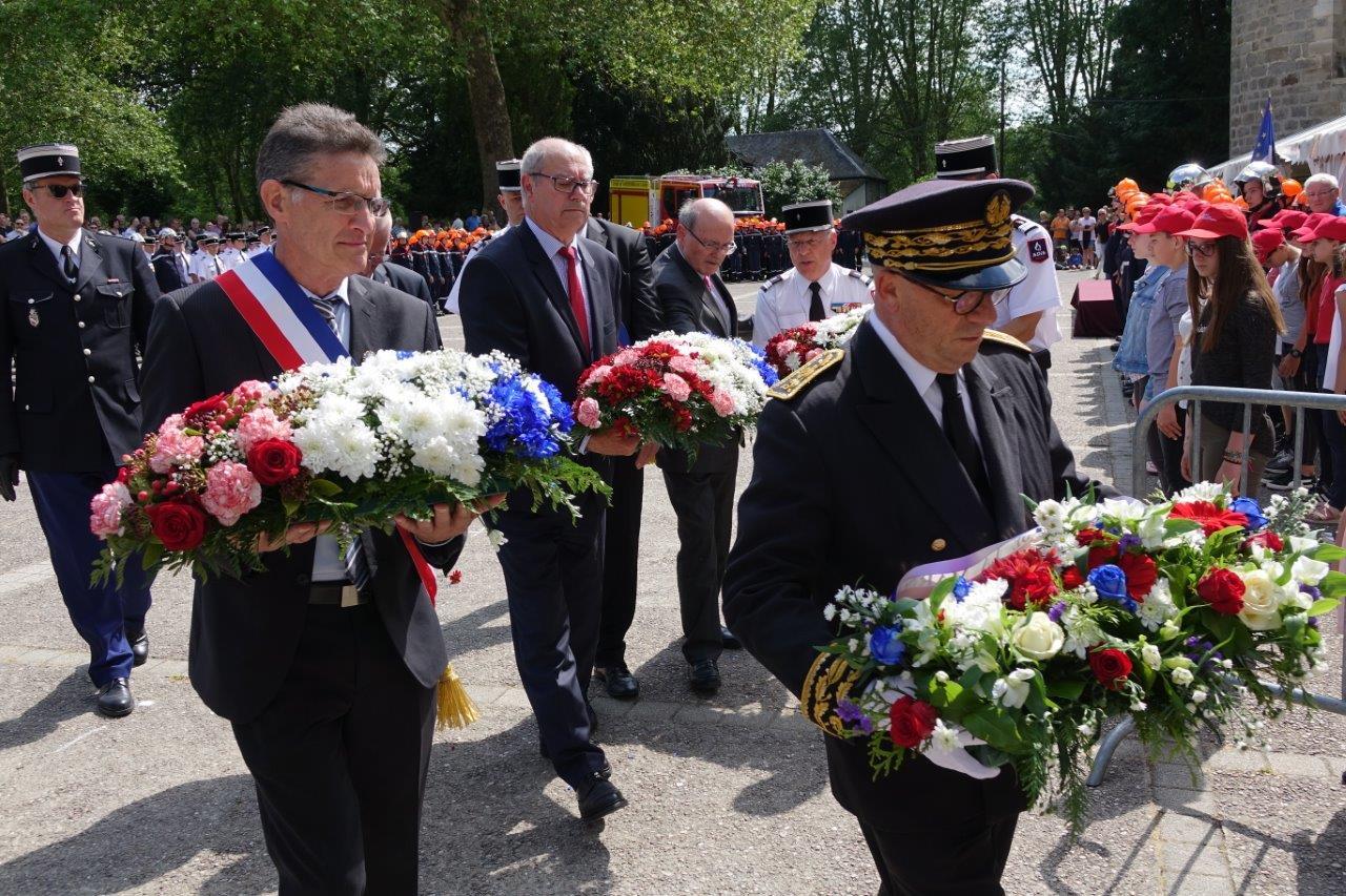 De gauche à droite : Michel Courteaux et Denis Conus déposent chacun une gerbe de fleurs en hommage aux sapeurs-pompiers morts en service.