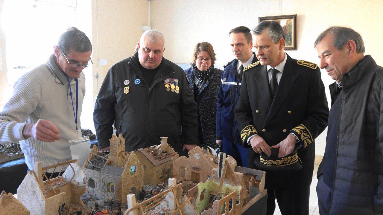A gauche, Christian Leclère présente la maquette d'un village français détruit au cours de la Grande guerre.