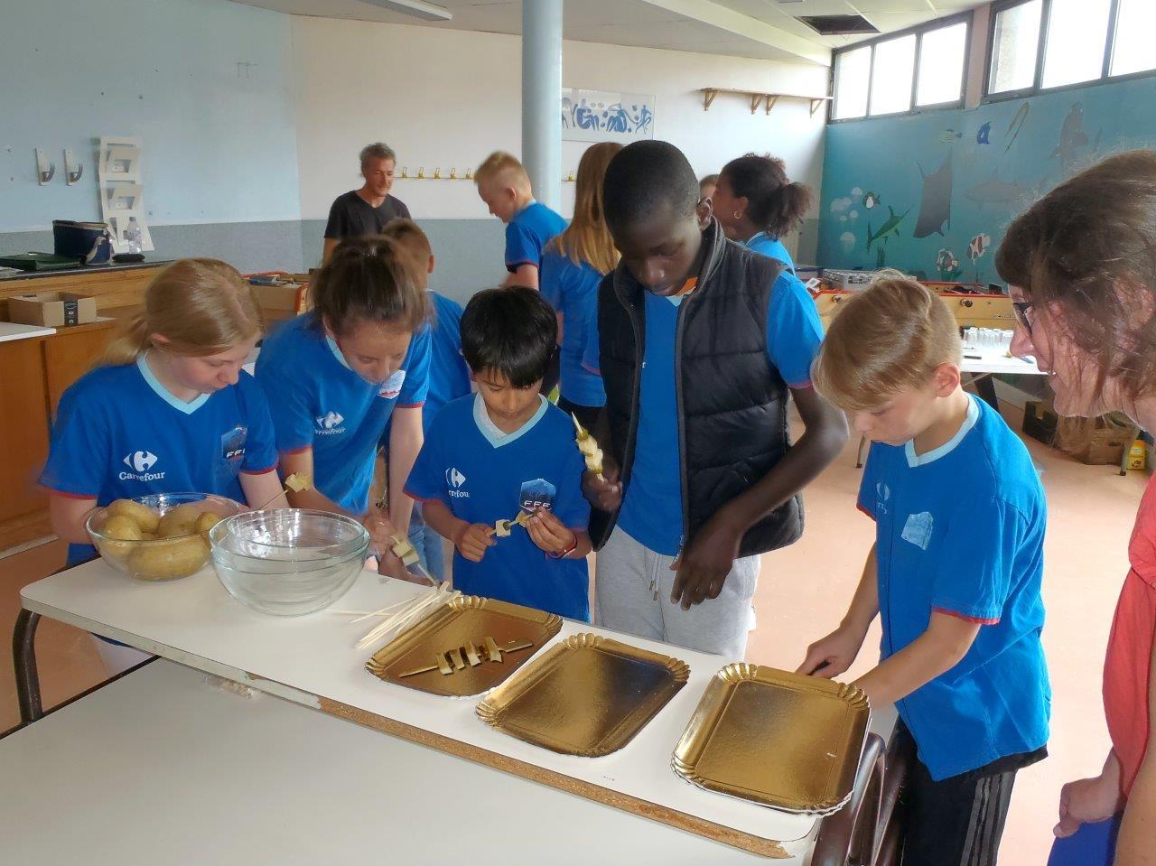 Les élèves préparent les brochettes d'Emmenthal et cornichons.