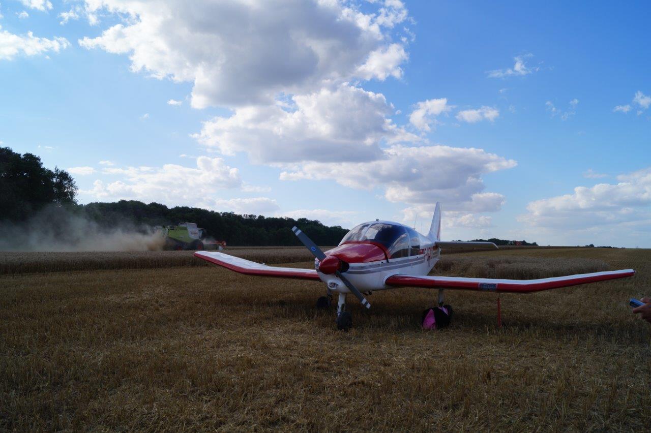 La parcelle de blé est moissonnée pour permettre le décollage de l'avion.