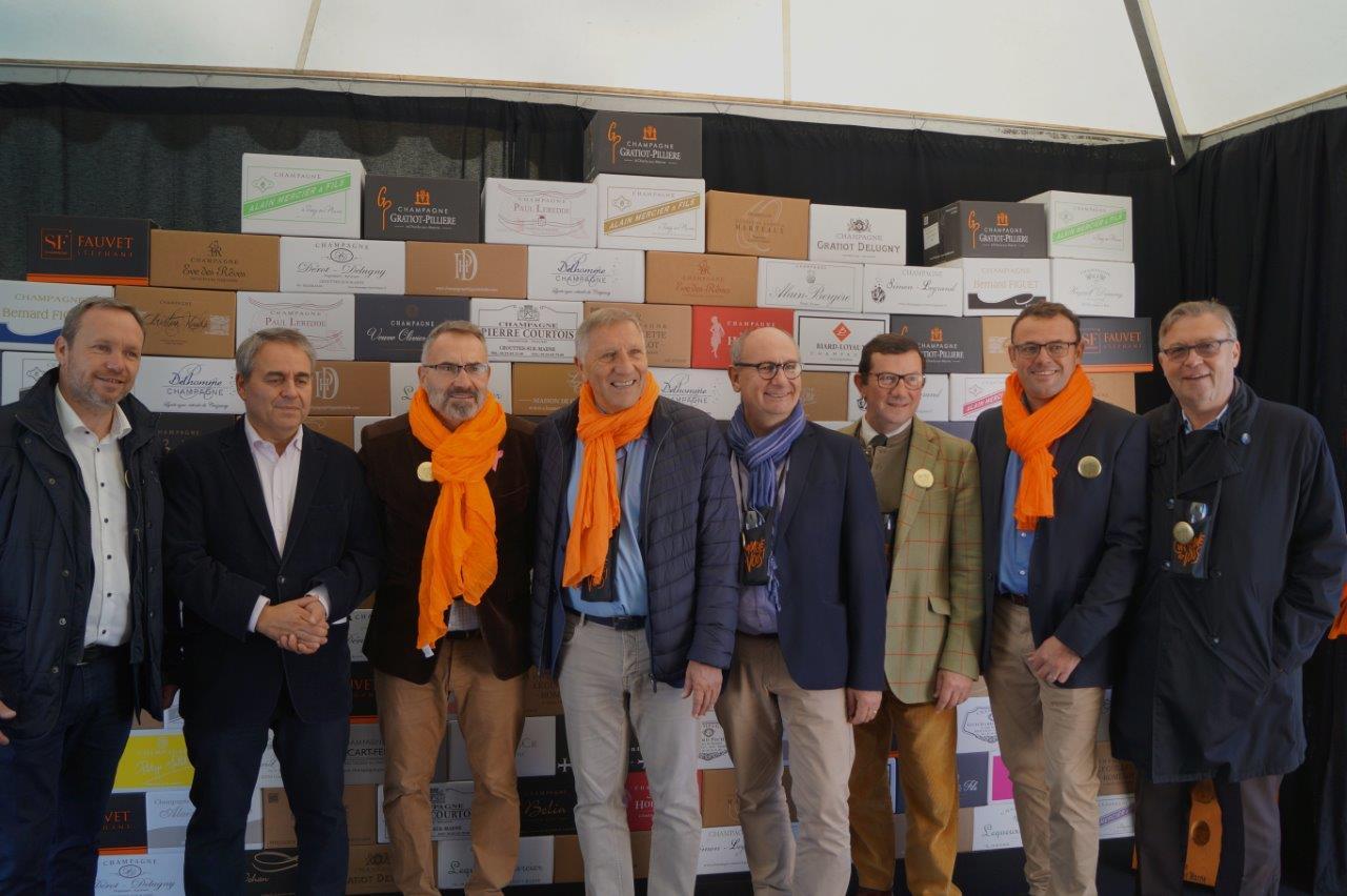 Les élus posent devant le mur monté en cartons de champagne.