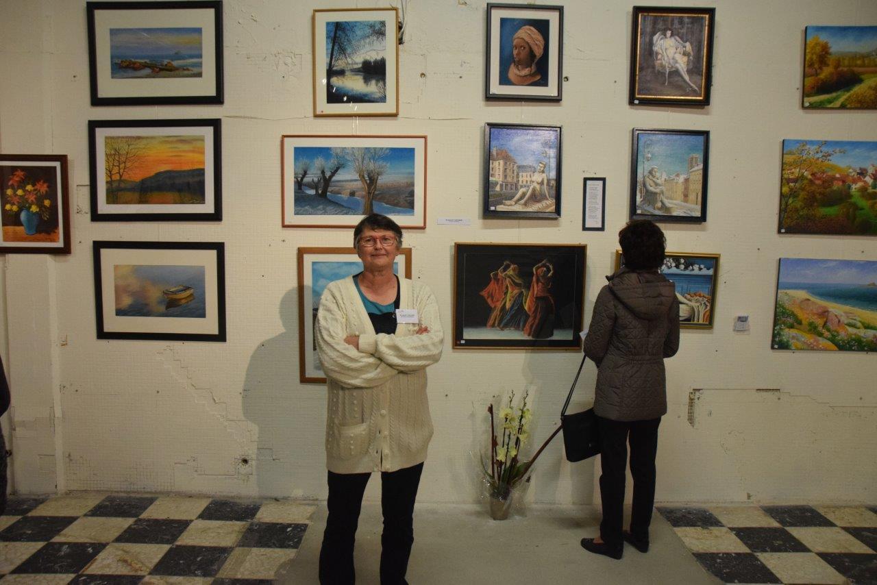 L'artiste Scarlett Vacher pose devant ses toiles.