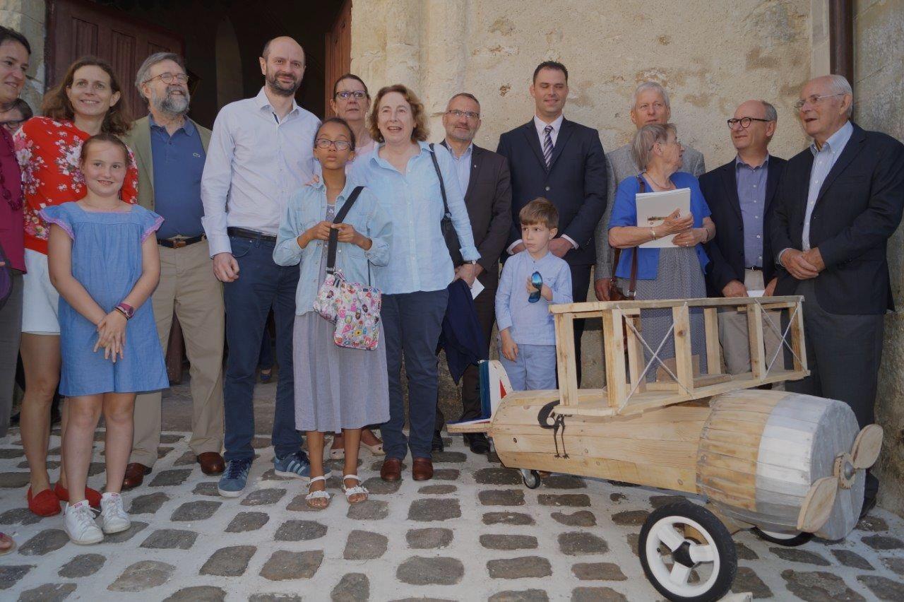 A la sortie de la messe, la famille de Xavier Moissinac et les élus posent près l'avion SPAD XIII construit en bois de palette par des bénévoles de la paroisse.