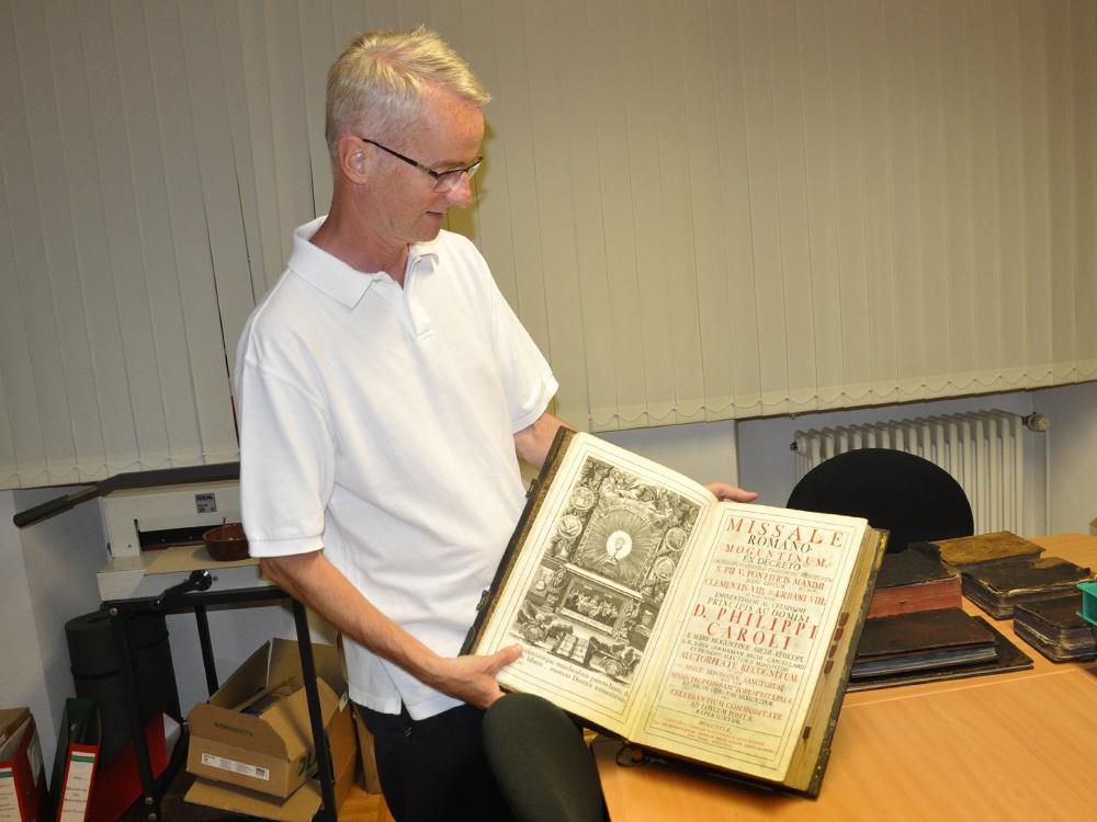 Pfarrer Korfmann zeigt ein  Messbuch aus dem 18. Jahrhundert