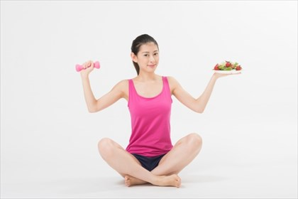 野菜サラダとダンベルを持った女性