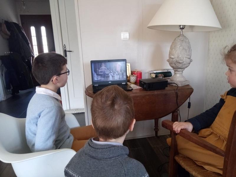 Les enfants sont regroupés devant l'ordinateur pour suivre la 1ère messe en confinement dimanche 15 mars dernier à la basilique