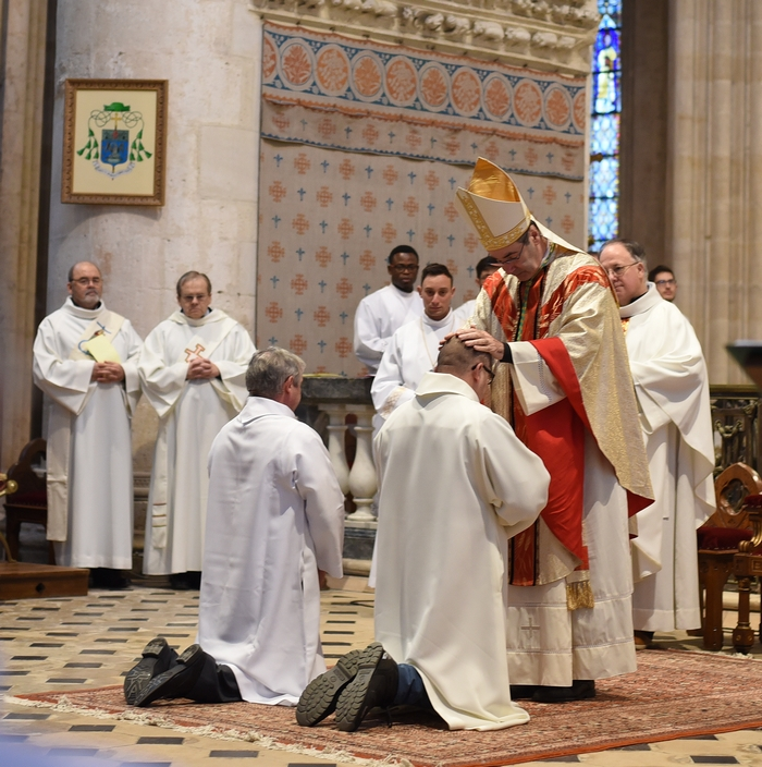 puis l'évêque leur impose les mains.