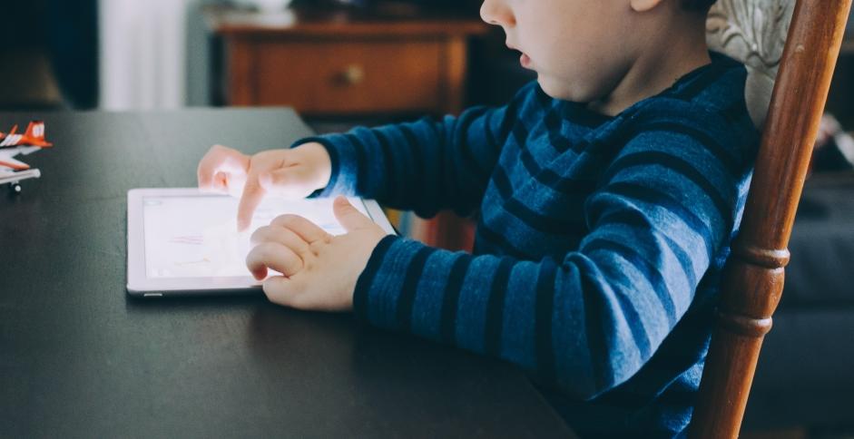 Un enfant utilisant une tablette tactile, donc soumis aux effractions digitales