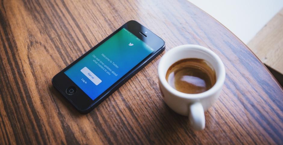 A côté d'une tasse de café, un iPhone avec la page de connexion de Twitter, premier risque d'effractions digitales