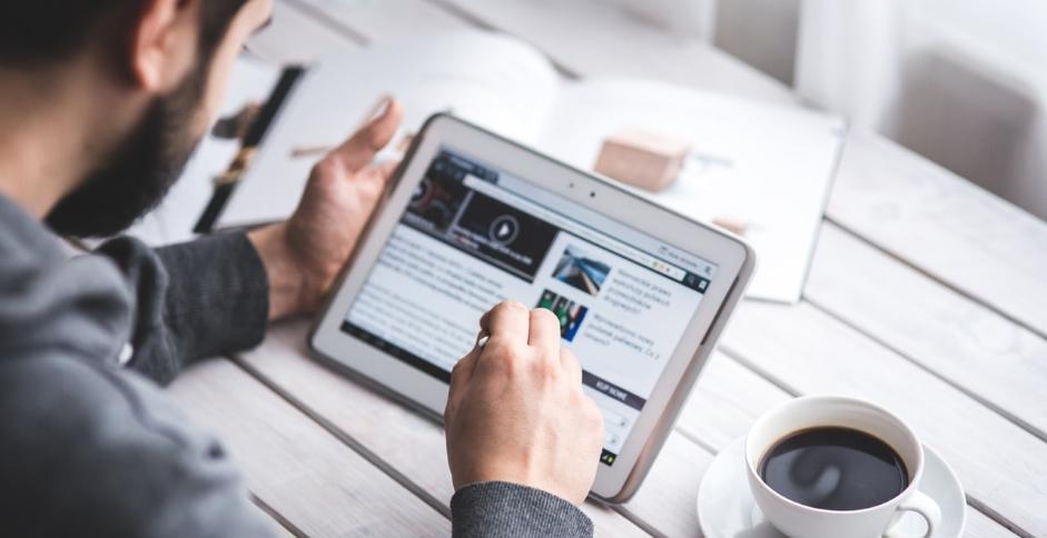 Un homme lisant sur sa tablette des articles traitant des effractions digitales