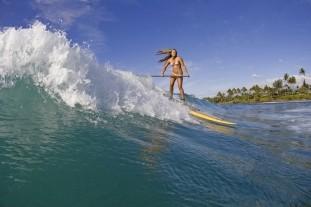 Frau beim SUP Surfen in der Welle