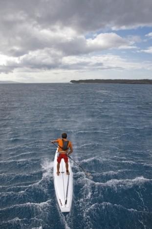 Actionfoto SUP Paddeln bei starkem Wind mit Coiled Leash zur Sicherheit