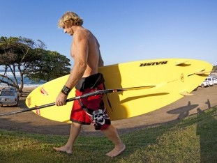Robby Naish trägt sein SUP Board an den Strand
