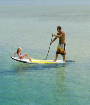 Stand Up Paddler mit Kind an Board