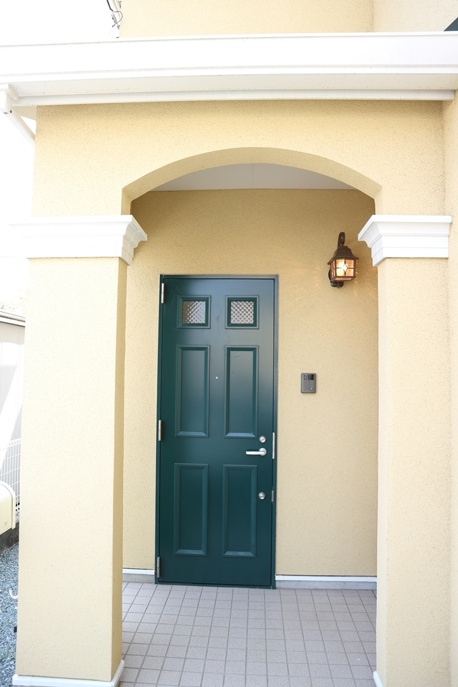 お洒落な玄関ポーチとグリーンの玄関扉が印象的