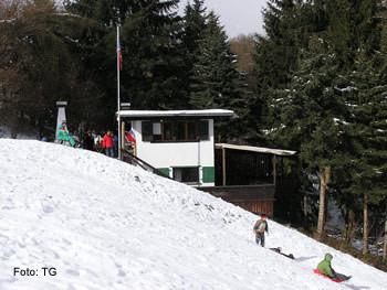 Skihütte: Kinder mit Schlitten unterwegs.