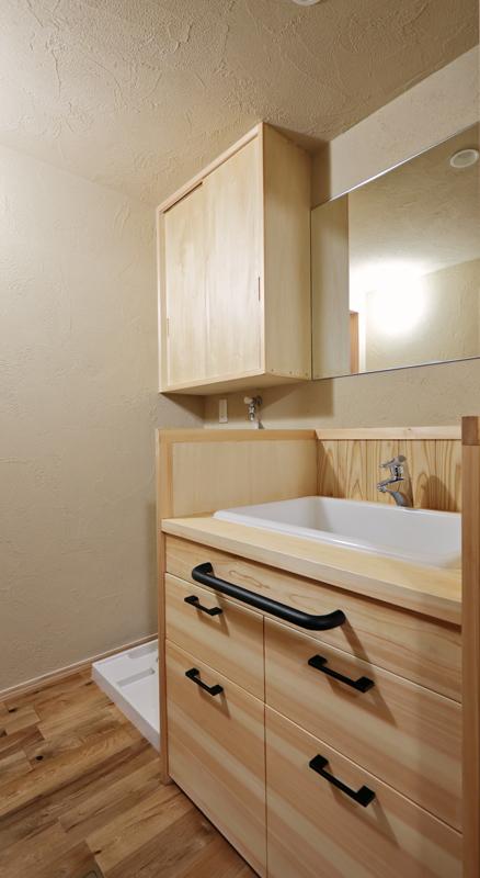 面材とカウンターに桧を使用した造作の洗面化粧台で鏡もオーダーメイドのものを使用