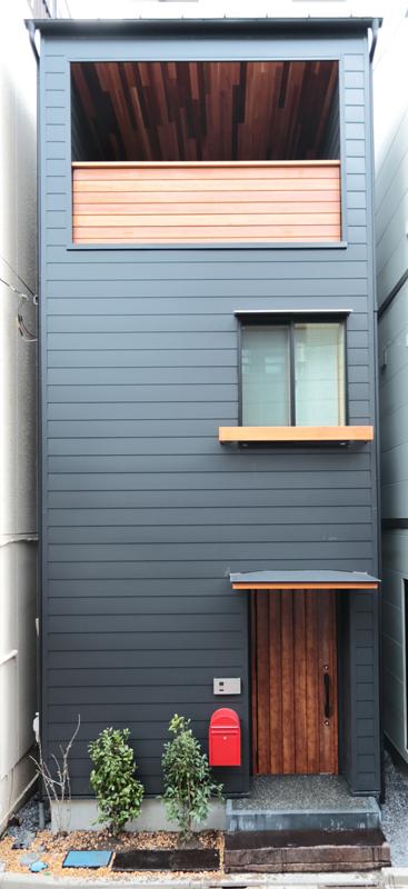 外壁には黒のガルバリウム鋼板を横張りにして玄関ポーチはモルタル洗い出しで仕上げました