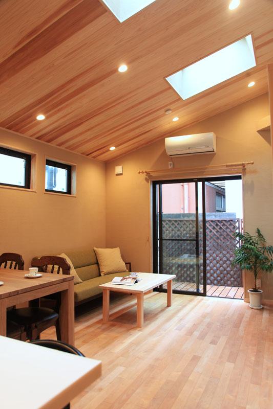 勾配天井を活かした広々リビングはトップライトからの採光で開放的で明るい雰囲気に