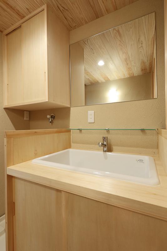 1階洗面室は桧を使用した造作洗面化粧台とオーダーメイドの鏡