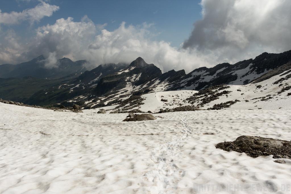 Der Weg führt durch Schnee und über Felsen - die zwei kleinen Punkte auf dem Schnee in der Mitte sind zwei Wanderer!